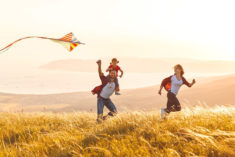 Young family running through a field while flying a kite